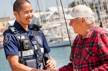 A fisheries Officer shaking hands with a fisherman