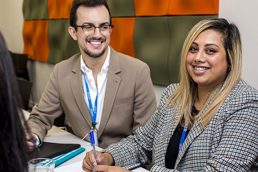 A man and women smiling while in an office setting.
