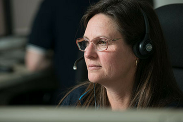 A female triple zero call taker on the phone